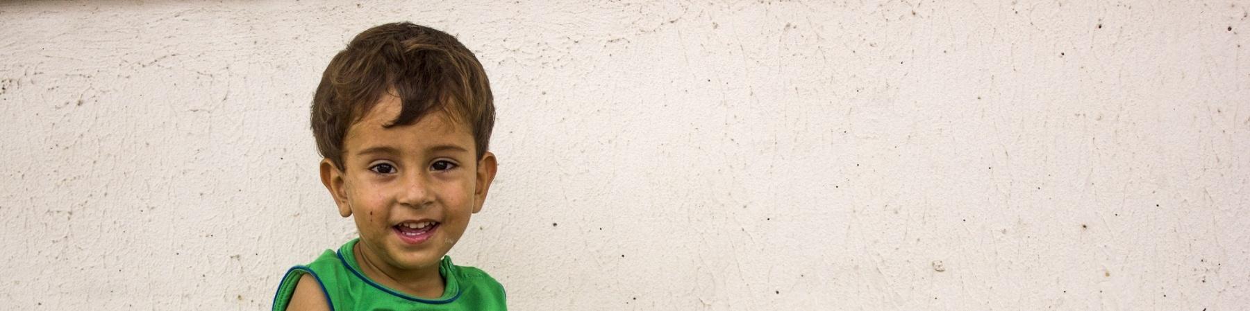 bimbo seduto a terra con le gambine aperte poggiato a un muro, vestito con maglietta verde e pantaloncino blu