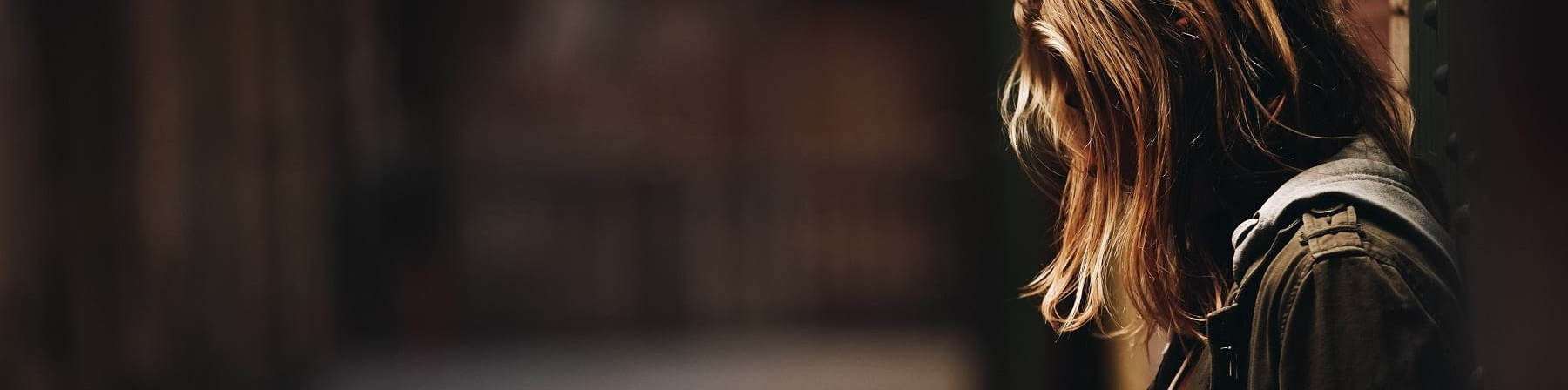 una ragazza bionda di profilo appoggiata con la schiena al muro. Guarda verso il basso e i capelli le coprono il viso. Indossa una giacca jeans e si vede sullo sfondo un corridoio vuoto e in semi oscurità.