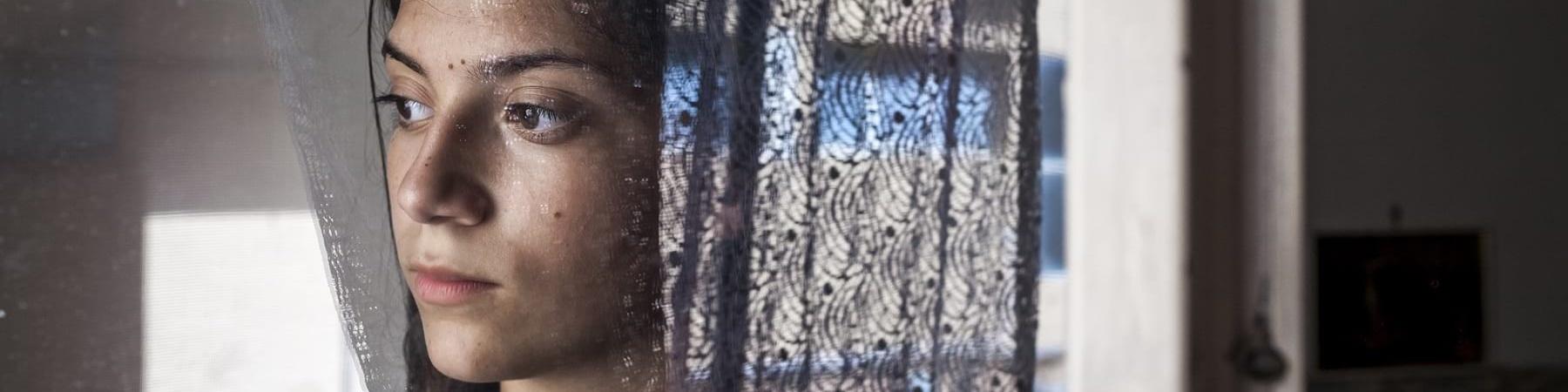 Primo piano di una ragazzina dietro il vetro di una finestra con la tendina celeste di lato