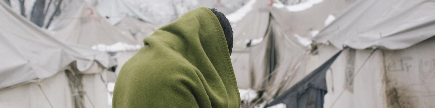 Minore avvolto di spalle avvolto in una coperta nel campo di Vucjak in Bosnia ed Erzegovina