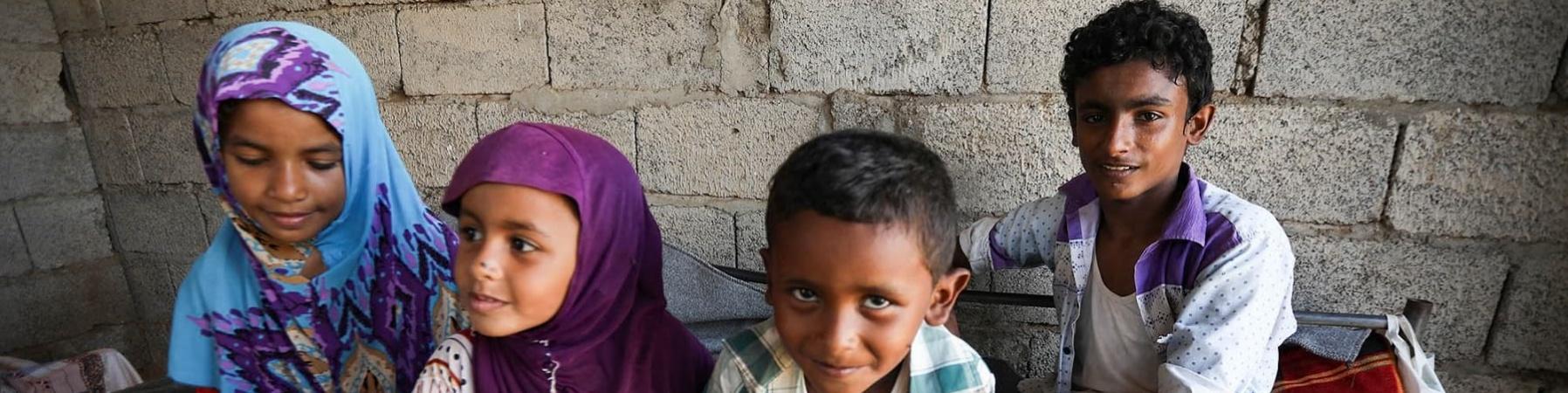 Quattro bambini yemeniti seduti sul letto insieme in una casa di mattoni
