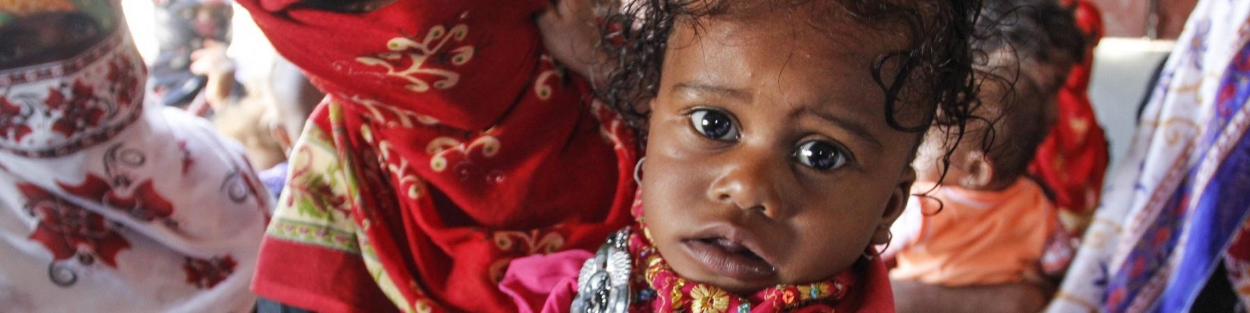 Bambina yemenita in primo piano e mamma dietro di lei coperta dal velo