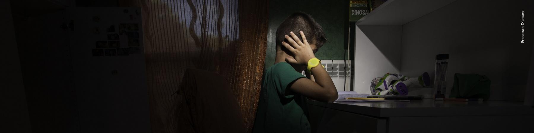 Bambino nella sua stanza buia si copre le orecchie con le mani
