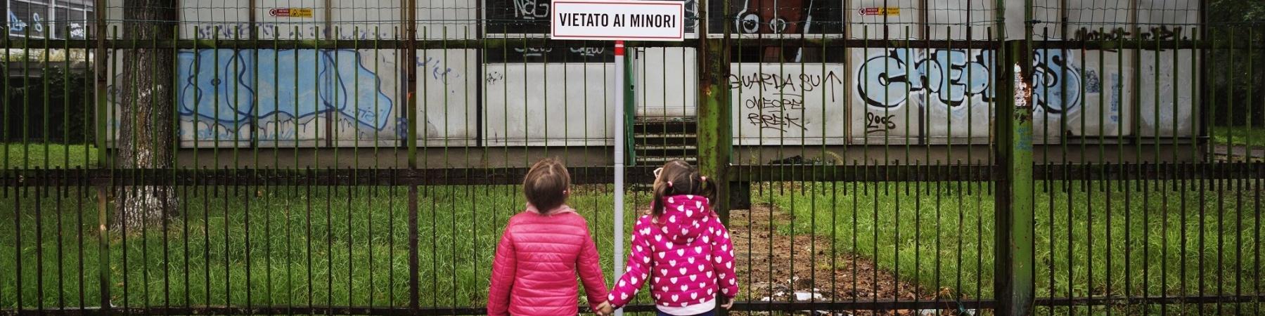 """due bambine si tengono per mano davanti a un cartello di divieto con scritto """"vietato ai minori"""""""