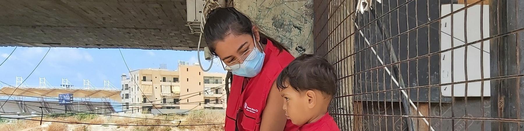 operatrice save the children con mascherina seduta su un muretto a fianco di un bimbo. Sullo sfondo varie presone che camminano.