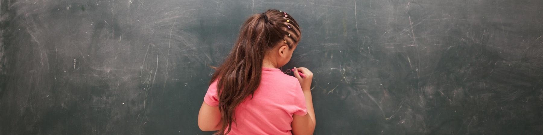 bambina di spalle davanti a una lavagna nera scrive con il gessetto