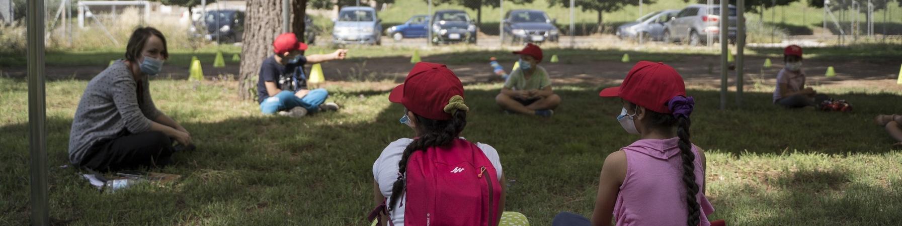 due bambine sedute sul prato di spalle che parlano con un operatrice