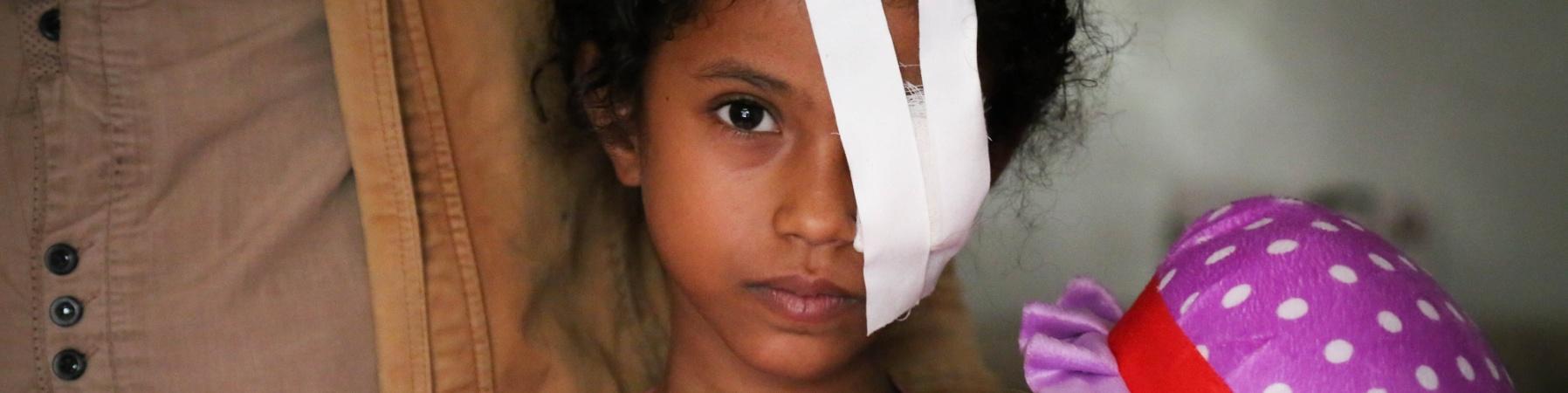 Bambina con benda su un occhio insieme al padre Yemen