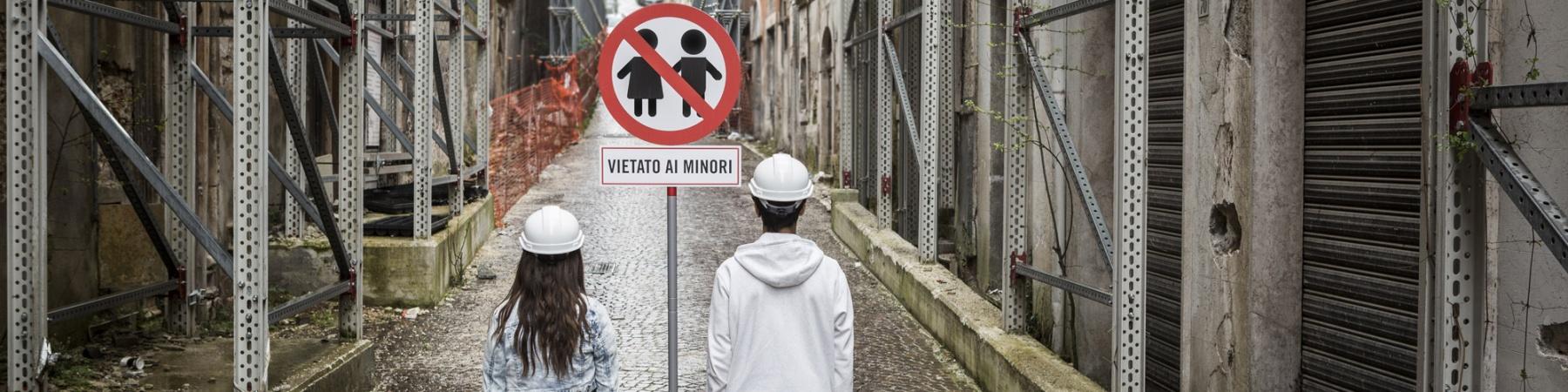 """Foto di bambini fermi davanti al cartello """"Vietato ai Minori"""""""