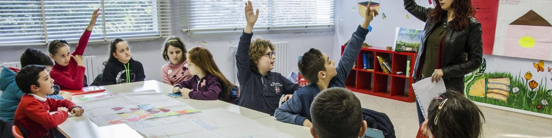 una decina di bambini seduti a un banco di scuola alzano la mano alla domanda della maestra
