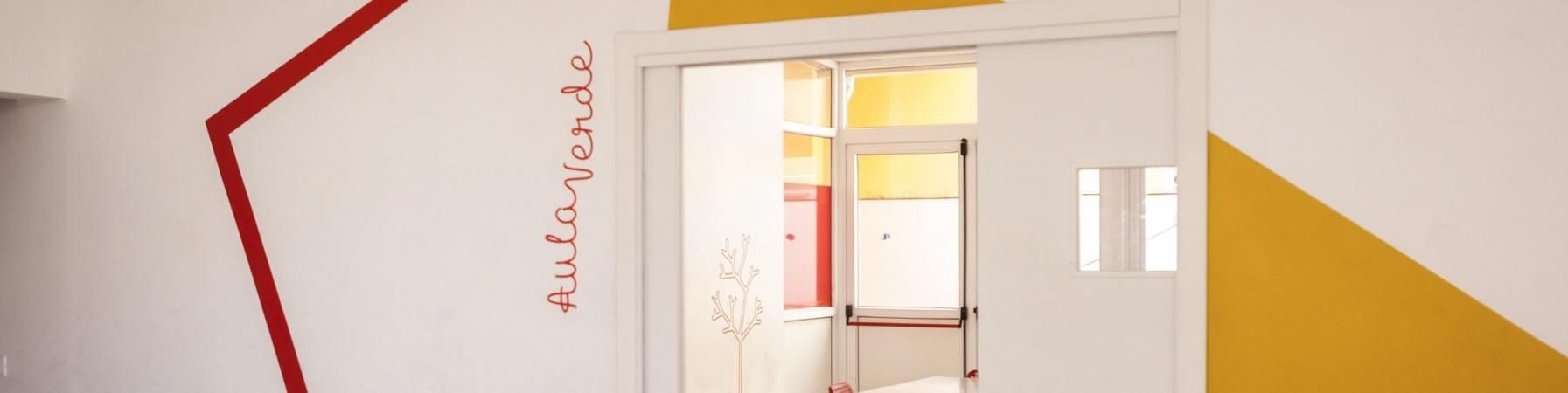 interno di un Punto Luce di Save the Children Italia, muro con disegnata una lampada da tavolo che illumina una porta verso una sala