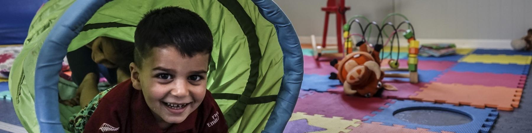 Bimbo gioca in un aula giochi passando attraverso un tunnel verde