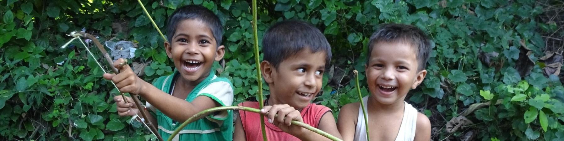 tre bambini indiani sorridenti con arco e freccia giocattolo che giocano insieme
