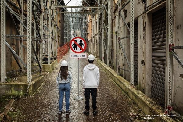 2 bambini nella zona rossa a L'Aquila con caschetto bianco di spalle davanti a cartello vietato ai minori