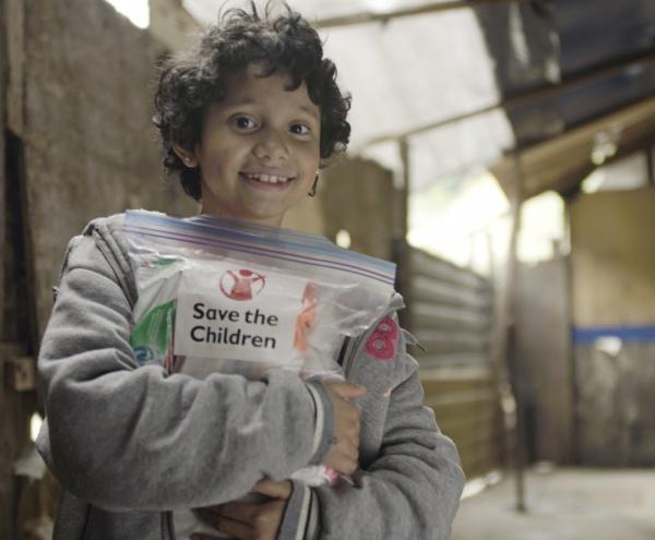 bambino che tiene stretto a se il kit fornito da Save the Children