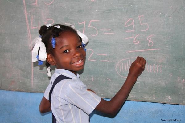 bimba che scrive alla lavagna a scuola e ci guarda con un grande sorriso. Vestita con una camicia azzurra ha un nastro tra i capelli pettinati con due treccine.