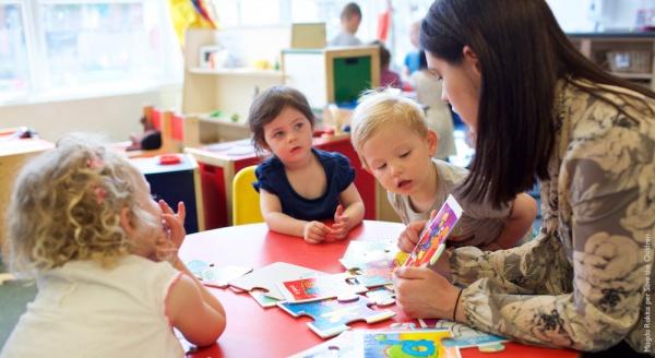 Insegnante d'asilo con tre bambini fanno i compiti al tavolo