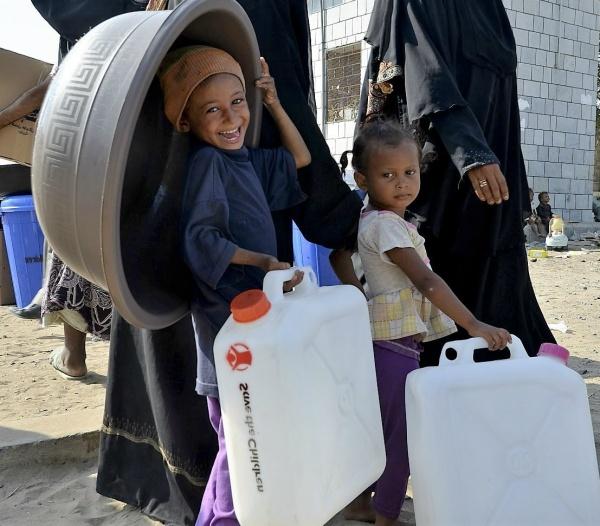 due bambini con due taniche dell'acqua