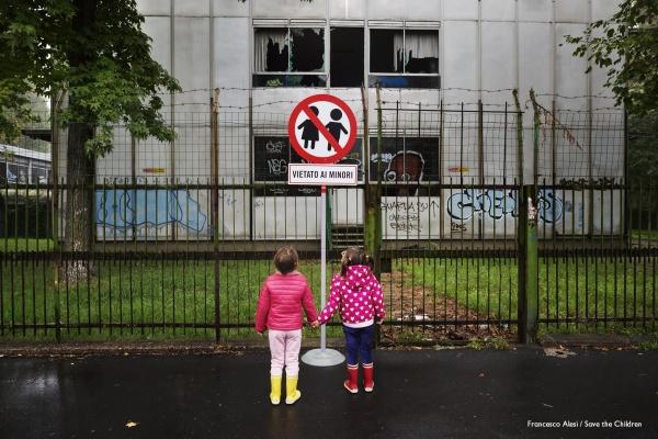 """due bambine si tengono per mano davanti a un cartello con un divieto con scritto """"vietato ai minori"""""""