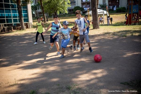 5 bambini giocano a calcio in un cortile alberato illuminato dal sole
