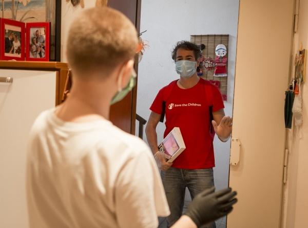 Un operatore di Save the Children consegna un tablet ad un bambino così che possa continuare a studiare durante l'emergenza sanitaria Covid-19