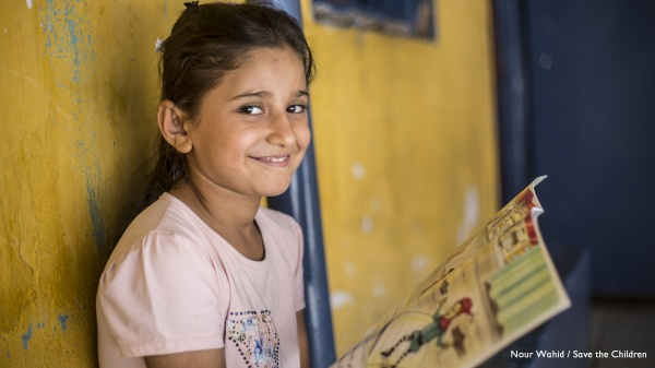 bambina guarda in camera sorridente con un libro in mano aperto