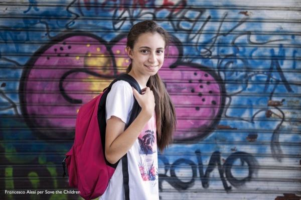 bambina con zaino in spalle che cammina davanti a un muro colorato e guarda verso di noi