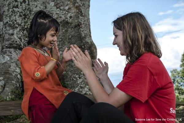 operatrice save the children gioca con una bambina nel prato