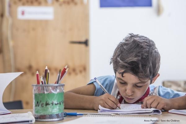 bambino al banco disegna con pastelli colorati su un foglio bianco