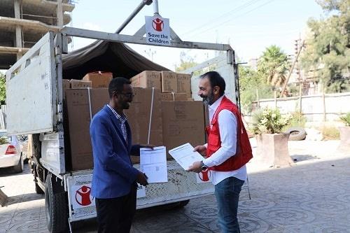 Un operatore di Save the Children consegna gli aiuti a un partner locale