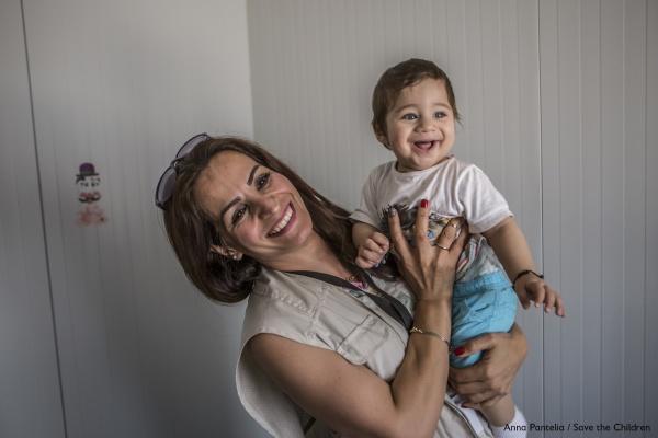operatrice save the children sorridente con in braccio una bimba sorridente