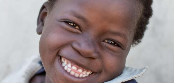 bambina di colore sorridente guarda verso di noi