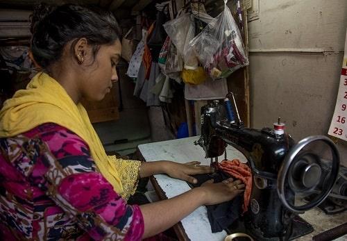 Una ragazza indiana, beneficiaria dei progetti di Save the Children, utilizza la macchina da cucito