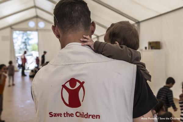 operatore umanitario di spalle tiene in braccio un bambino