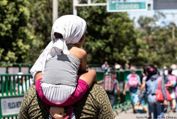 bambina di spalle sulle spalle della sua mamma