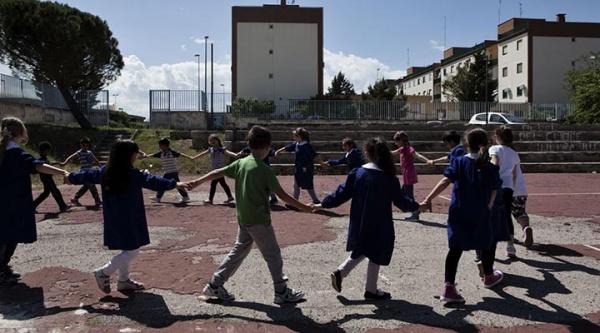 Bambini in cerchio giocano al girotondo in un parco