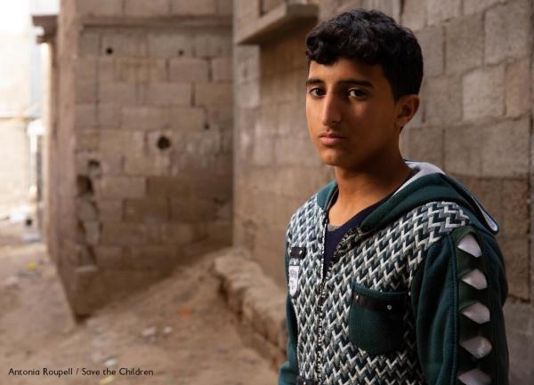 ragazzo palestinese con felpa grigia guarda verso di noi con sguardo triste