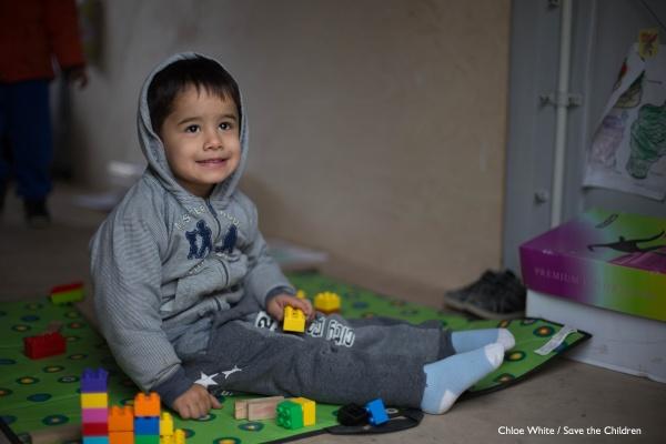 bimbo con felpa con cappuccio seduto per terra su un tappeto dei giochi con giochi intorno a sè