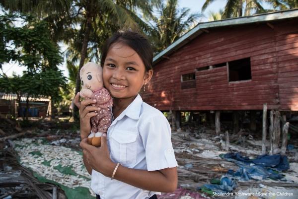 bambina sorridente con un peluches in braccio davanti a una casetta in legno con intorno detriti post emergenza