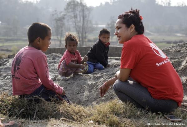 operatrice Save the Children che parla in un prato con tre bambini