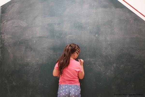 bambina alla lavagna girata di spalle scrive con un gessetto
