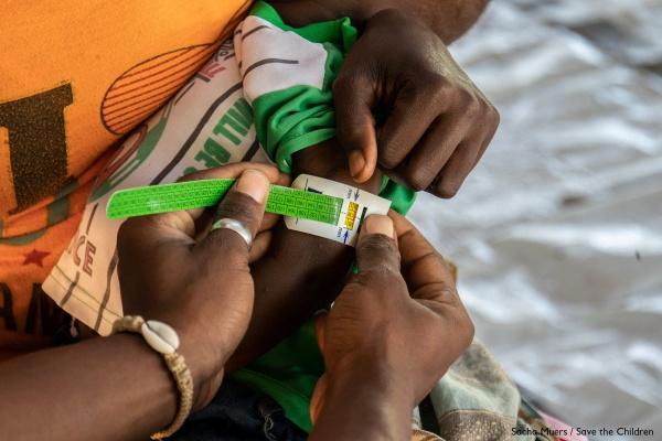 dettaglio di due mani che misurano il polso di un bambino per controllare lo stato di salute e di malnutrizione