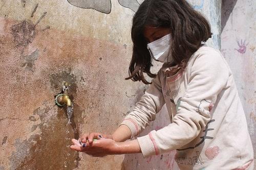 Una bambina siriana, che indossa una mascherina, si lava le mani per prevenire il contagio di Covid-19