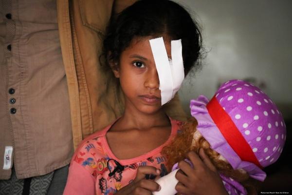 Bambina con occhio bendato con in braccio peluches