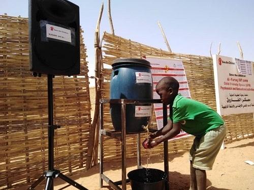 Un bambino in Sudan si lava le mani per proteggersi dal Coronavirus a una postazione idrica attrezzata da Save the Children