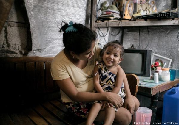 una mamma tiene in braccio sulle gambe la sua figlia sorridente. Entrambe sono in casa.