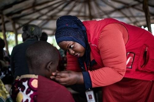 Una operatrice in Uganda controlla lo stato di salute di un bambino