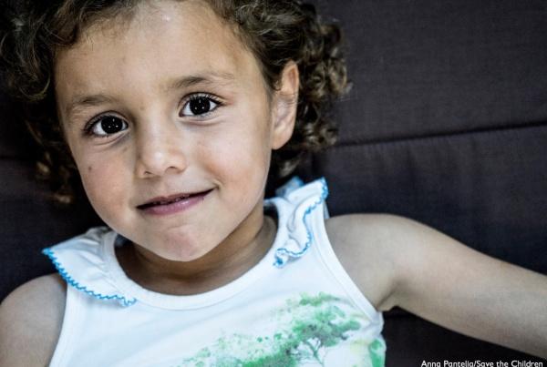 primo piano bambino sorridente con occhi scuri e capelli castani