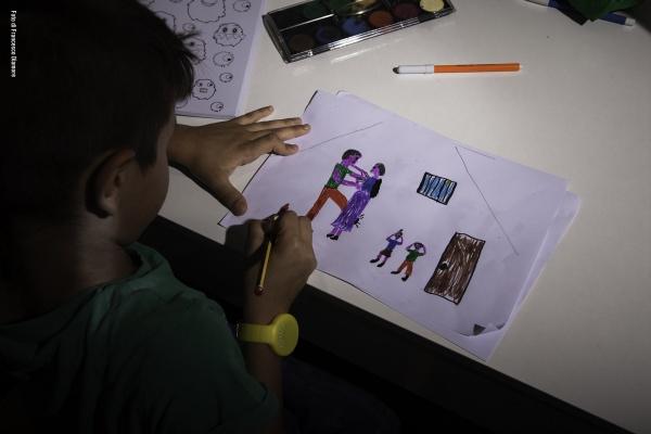 Bambino in camera disegna alla scrivania