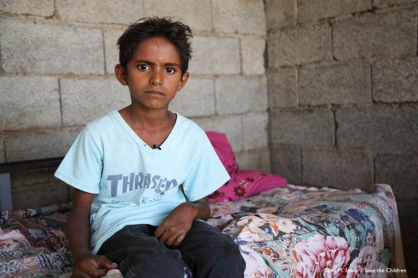 bambino yemenita seduto sul letto con sguardo molto triste